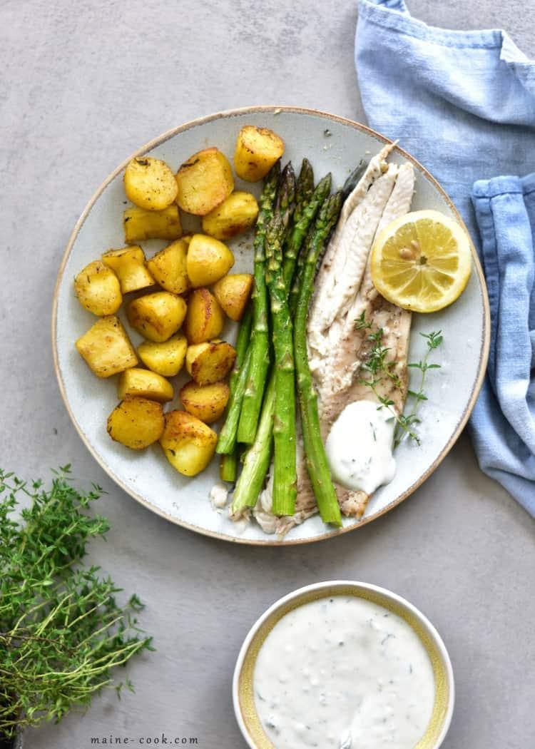 Pieczony pstrąg z ziemniakami, szparagami i ziołowym dipem Whole roasted trout with potatoes, asparagus and thyme-garlic sauce