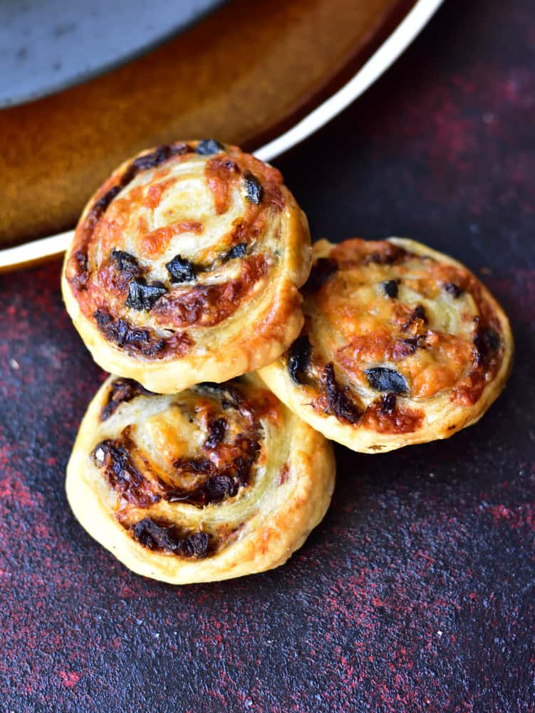 sun-dried tomato, olive and cheese puff pastry pinwheels on a red-violet background