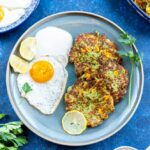 zucchini and corn fritters with fried egg on a blue plaze