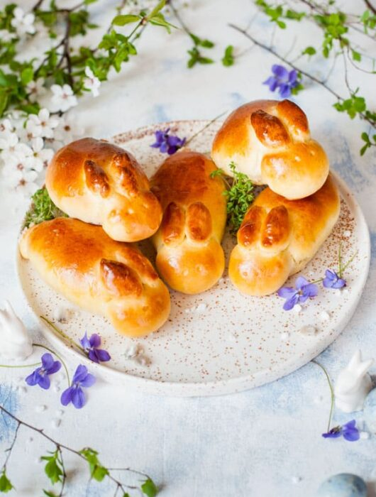 easter bunny rolls on a white plate, flowers in the background