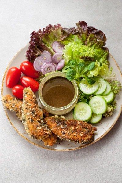 składniki sałatki z kurczakiem w panierce z pestek dyni na talerzu
