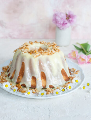 almond bundt cake on a white plate, covered with chocolate glaze and flaked almonds