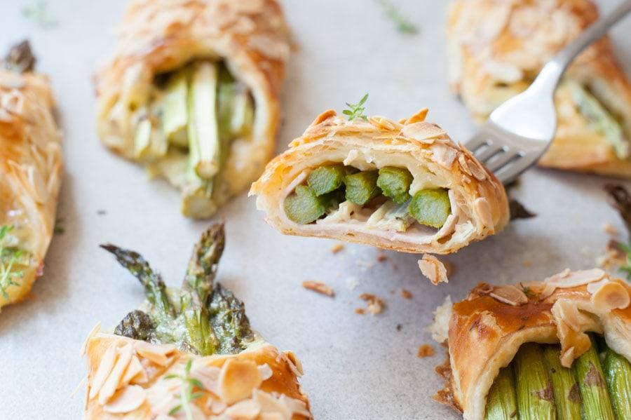 Szparagi w cieście francuskim z szynką i serem, przekrojone na pół