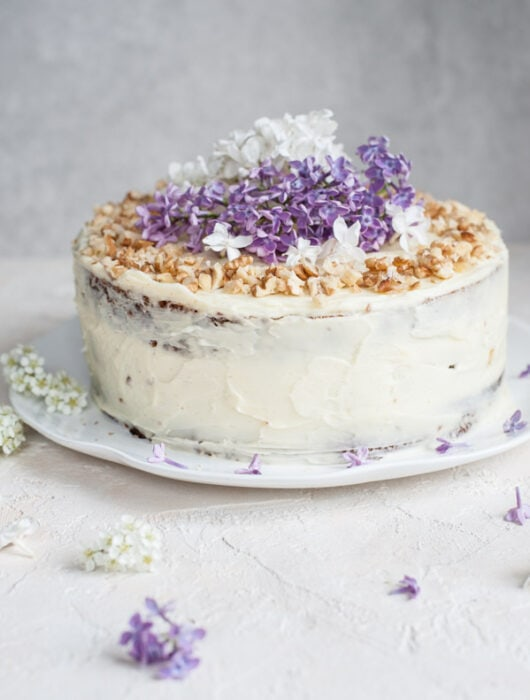 carrot layer cake with cream cheese frosting decorated with flowers and nuts