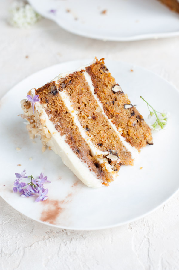 A piece of carrot layer cake with cream cheese frosting on a plate