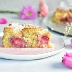 a slice of coconut cake with strawberries on a rose plate