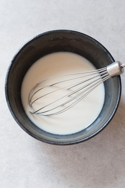 coconut liqueur, vanilla extract and yogurt in a black bowl