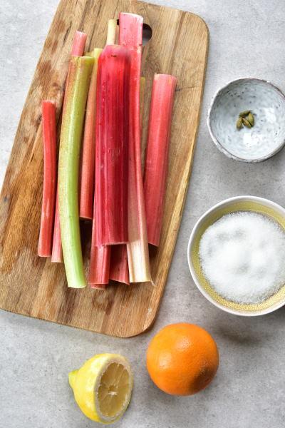 rabarbar na desce do krojenia, pomarańcza, ksylitol i kardamon z boku