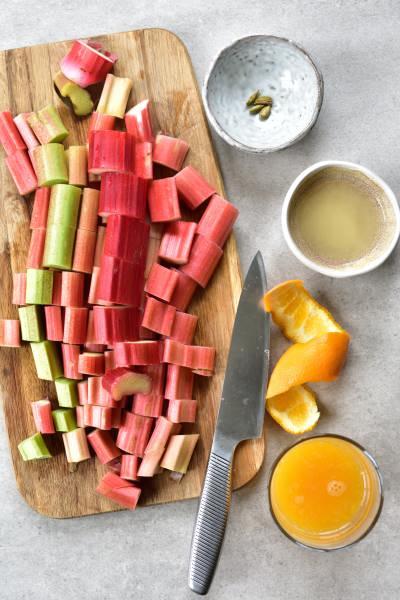 Pokrojony rabarbar na desce do krojenia, sok z pomarańczy i cytryny