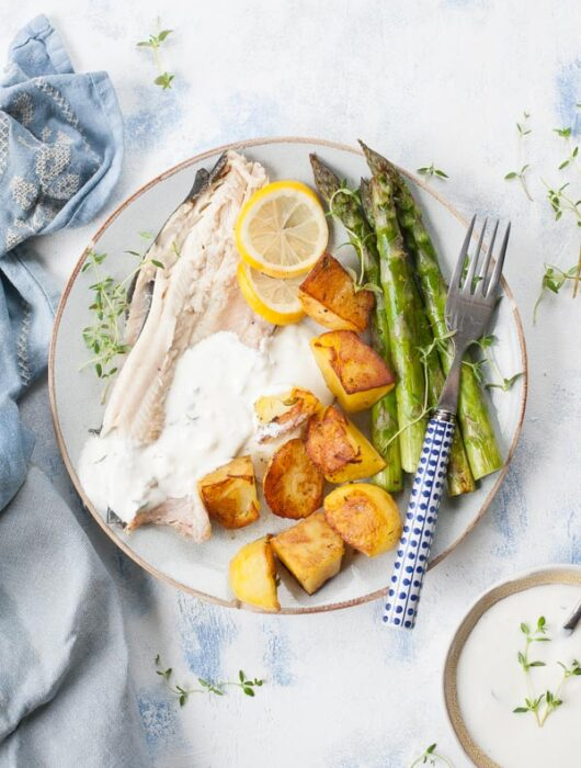 roasted trout with potatoes, asparagus and yogurt dip on a blue plate