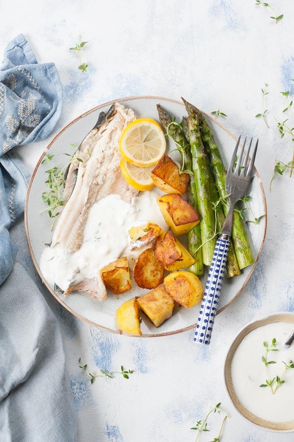 Zbliżenie na pieczonego pstrąga z ziemniakami, szparagami i ziołowo-czosnkowym dipem na talerzu