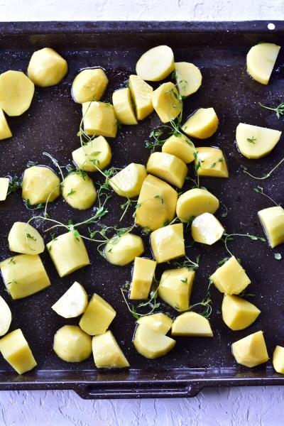 Ziemniaki i tymianek rozłożone na blaszce do pieczenia
