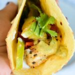 close up photo of tacos filled with chicken fajitas, bell peppers and onions