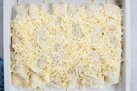 zawinięte naleśniki na blaszce do pieczenia posypane serem