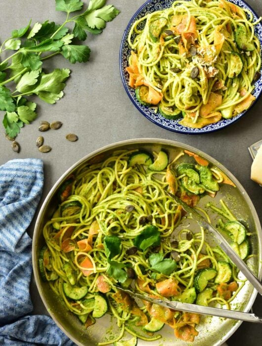 Parsley pesto pasta with zucchini and carrots in a pan.