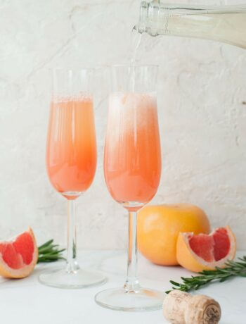 two champagne glasses filled with grapefruit mimosa
