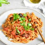 spaghetti alla puttanesca on a blue plate