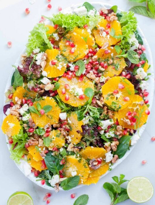 orange pomegranate salad with mint lime dressing on a white plate