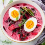 young beet soup in a white bowl, cooked eggs and dill in the soup