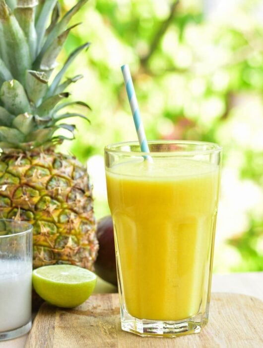 pineapple mango coconut smoothie in a glass on a wooden board