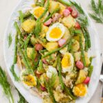 potato and asparagus salad on a white plate