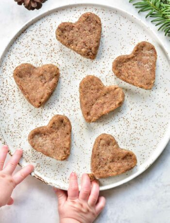heart-shaped soft gingerbread cookies for babies on a white plate, baby hands reaching for cookie