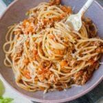szybkie spaghetti z mięsem i sosem ze świeżych pomidorów nabite na widelec w fioletowej misce