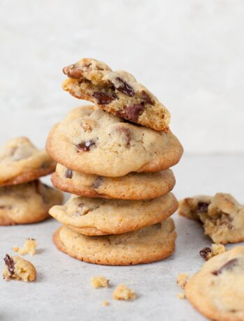 A stack of chocolate chip pecan cookies. Crumbled cookies scattered around.