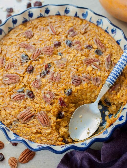 A close up picture of baked pumpkin oatmeal in a baking dish with a serving missing.