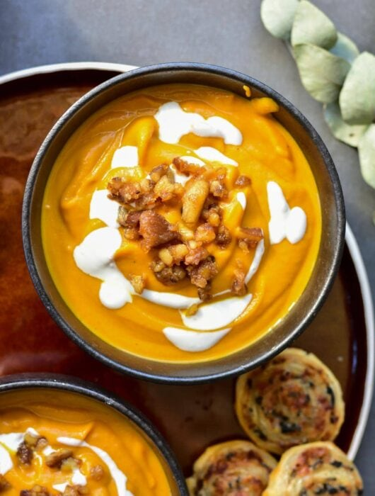 Pumpkin chestnut soup in a black bowl topped with yogurt and caramelized chestnuts.