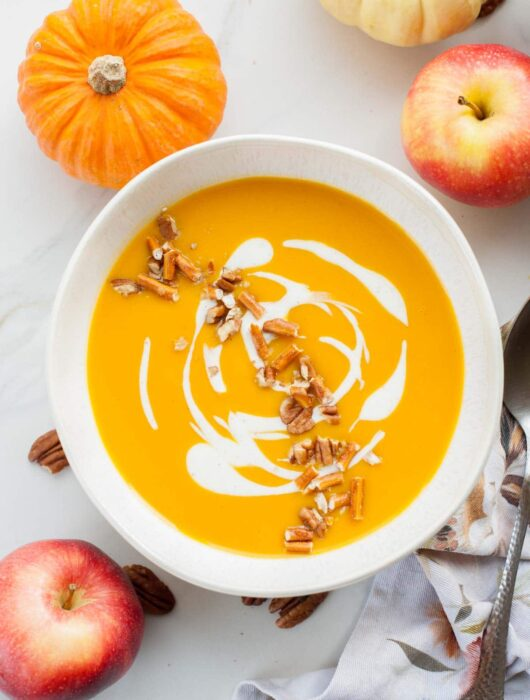 White bowl with butternut squash and apple soup. Apples in the background.