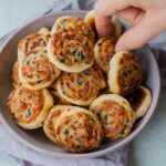 Puff pastry pinwheels with cheese, sun-dried tomatoes and olives in a violet bowl.