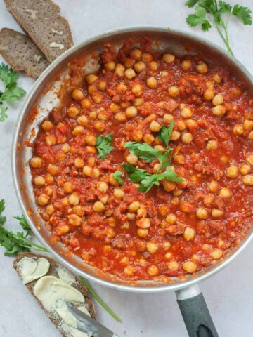Chickpeas with chorizo in spicy tomato sauce in a silver frying pan.