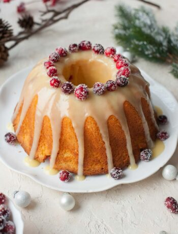 Cranberry orange bundt cake with white chocolate orange glaze and sugared cranberries.