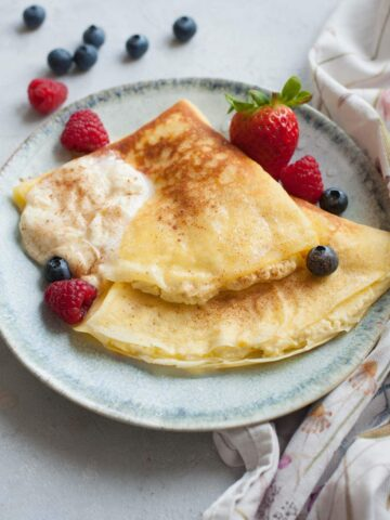 Nalesniki with cheese filling on a green plate. Berries and whipped cream on the side.
