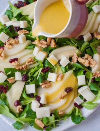 Lemon dijon vinaigrette is being poured over a pear walnut salad with cranberries and goat cheese.