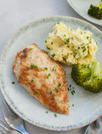 Parmesan mayo chicken on a green plate with mashed potatoes and broccoli.