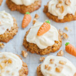 Carrot cake cookies with cream cheese frosting on a piece of parchment paper topped with marzipan carrots and nuts.