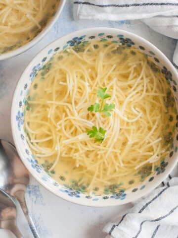 Rosół soup in a white blue bowl served with pasta and topped with parsley.