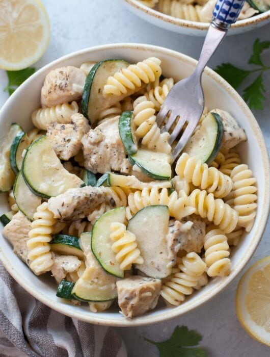 Chicken zucchini pasta in a white bowl is being picked with a fork.