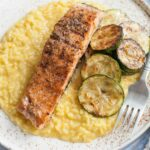 Saffron risotto with grilled salmon and zucchini on a white plate.